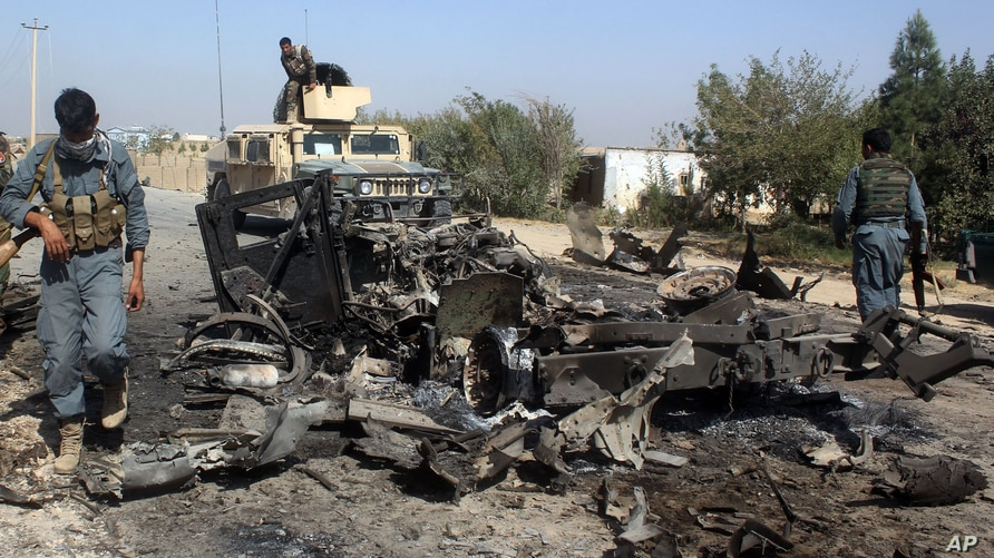 FILE - Afghan security forces inspect the site of a U.S. airstrike in Kunduz city, north of Kabul, Afghanistan, Oct. 2, 2015. T