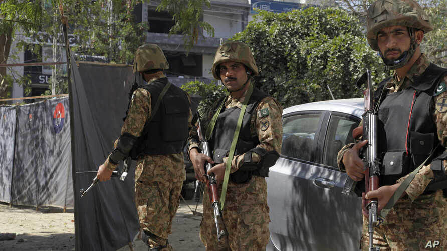 Pakistani soldiers stand alert at the site of an explosion, in Lahore, Pakistan, Thursday, Feb. 23, 2017. A Pakistani provincial minister says an explosion has killed at least eight people in the eastern city of Lahore.