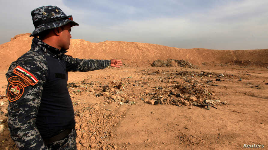 A member of Iraqi security forces gestures towards a mass grave for corpses in the town of Hammam al-Alil which was seized from Islamic State last week, Nov. 9, 2016.