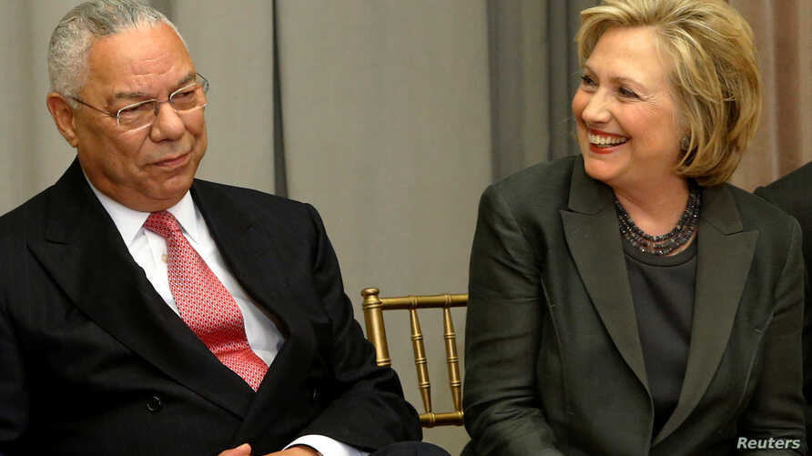 FILE - Former U.S. Secretaries of State Colin Powell (L) and Hillary Clinton (R) listen to remarks at a groundbreaking ceremony for the U.S. Diplomacy Center at the State Department in Washington, Sept. 3, 2014.