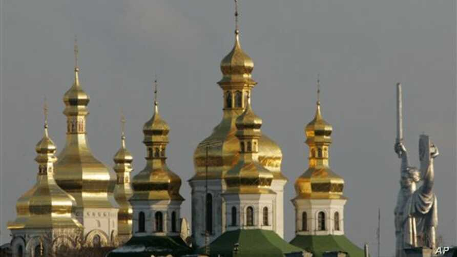 FILE - Golden cupolas of the 11th century Monastery of the Caves, holiest site of Orthodox Christians, beside the Soviet-era 62-meter tall Motherland statue, Kyiv.