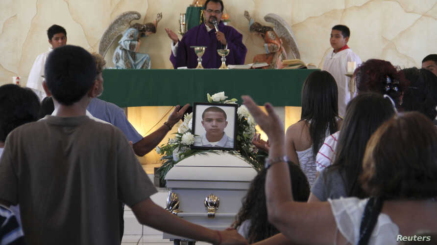 Relatives pray beside a coffin containing 16-year-old Jose Antonio Elena Rodriguez during his funeral in Nogales, Mexico, Oct.14, 2012.