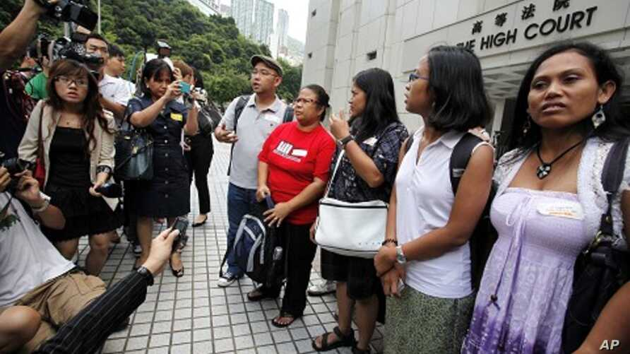 Eman Villanueva (L), vice chairperson of the Filipino Migrant Workers Union, and Dolores Balladares (2nd L), chairperson of United Filipinos in Hong Kong, along with other representatives, meet journalists outside the High Court in Hong Kong August 2