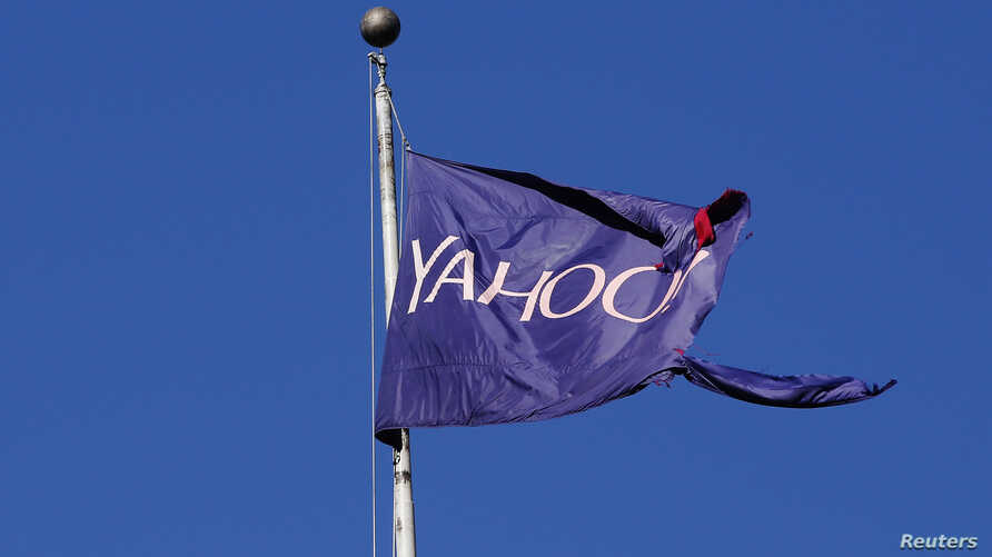 A flag bearing the Yahoo company logo flies above a building in New York, U.S., October 31, 2016. The European Commission has asked the U.S. about a secret court order Yahoo used to scan thousands of customer emails.