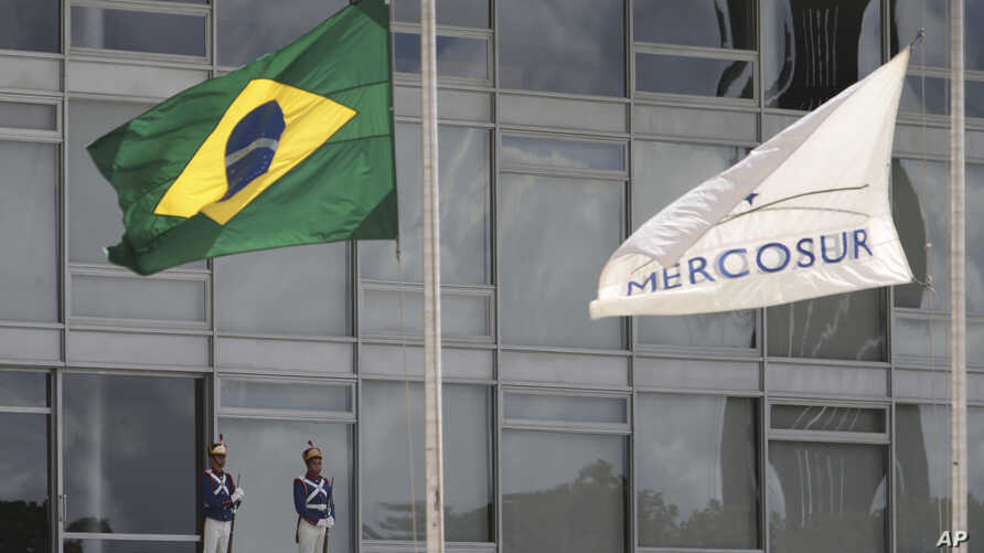 The Brazilian national flag along with a MERCOSUR banner fly at half-staff to honor plane crash victims, outside the Planalto Presidential Palace in Brasilia, Brazil, Nov. 29, 2016.