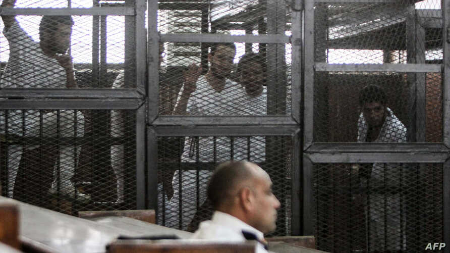 Defendants who are in custody stand in the accused cells during the trial of 20 individuals, including five Al-Jazeera journalists, for allegedly defaming the country and ties to the blacklisted Muslim Brotherhood on May 3, 2014.