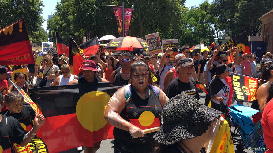 People carry Australian Aboriginal flags during a demonstration on Australia Day in Sydney, Jan. 26, 2019.
