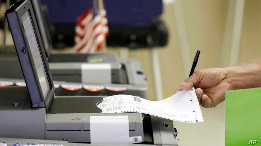 FILE - A voter casts his primary ballot in Hialeah, Fla. Paper ballots protect against electronic hackers, a Johns Hopkins University cryptography expert says.