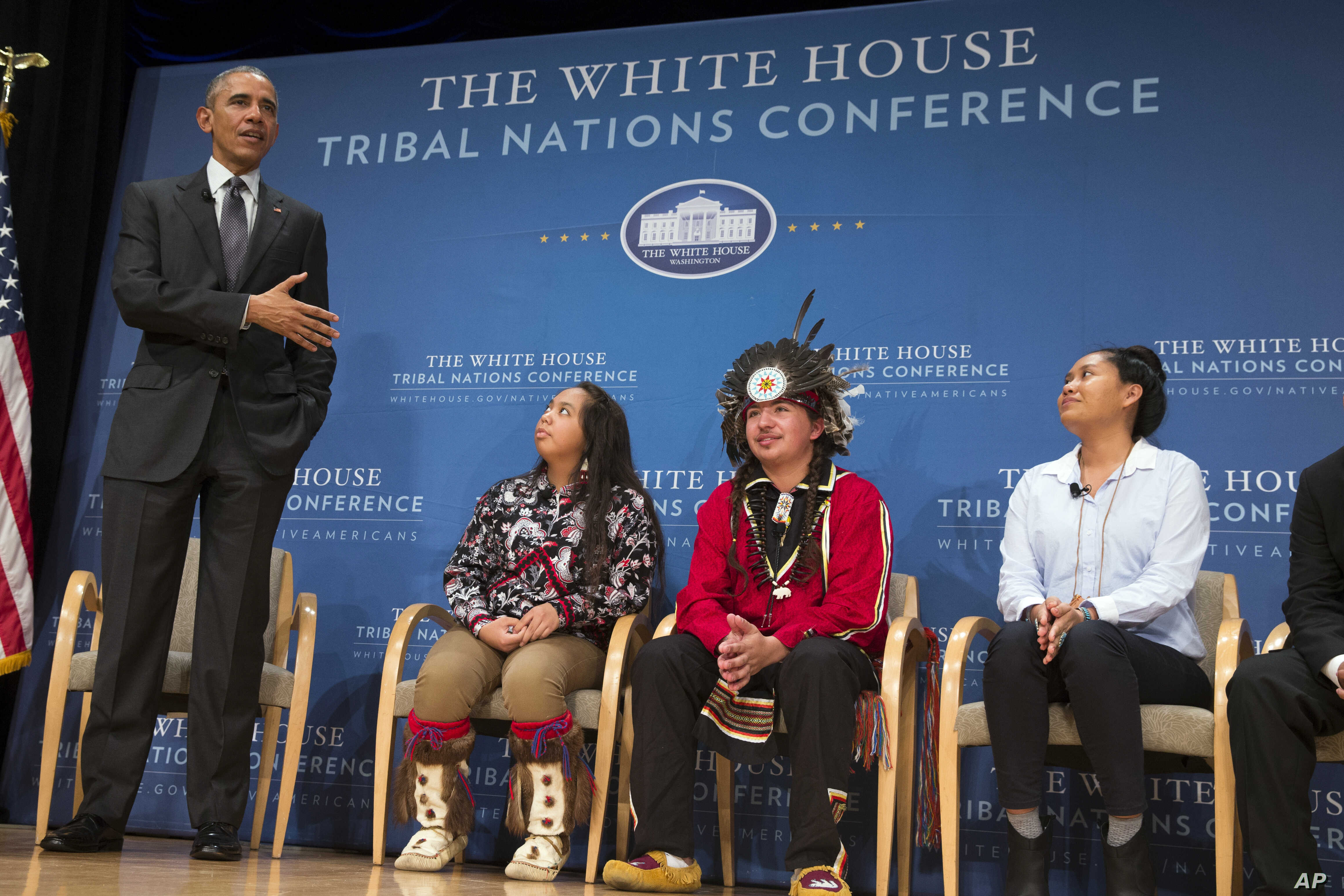 President Barack Obama speaks as, from left, Tatiana Ticknor of the Yup'ik/Tlingit/Dena'ina, Brayden White of the St. Regis Mohawk Tribe and Blossom Johnson of the Navajo Nation listen during the 2015 White House Tribal Nations Conference, Nov. 5, 20