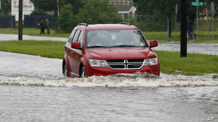 A driver attempts to steer through the remaining floodwaters from Harvey on Legion Street in Lake Charles, La., Aug. 29, 2017.