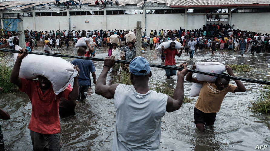People loot sacks of rice from a warehouse surrounded by flood waters from Cyclone Idai, in Beira, Mozambique, March 20, 2019.