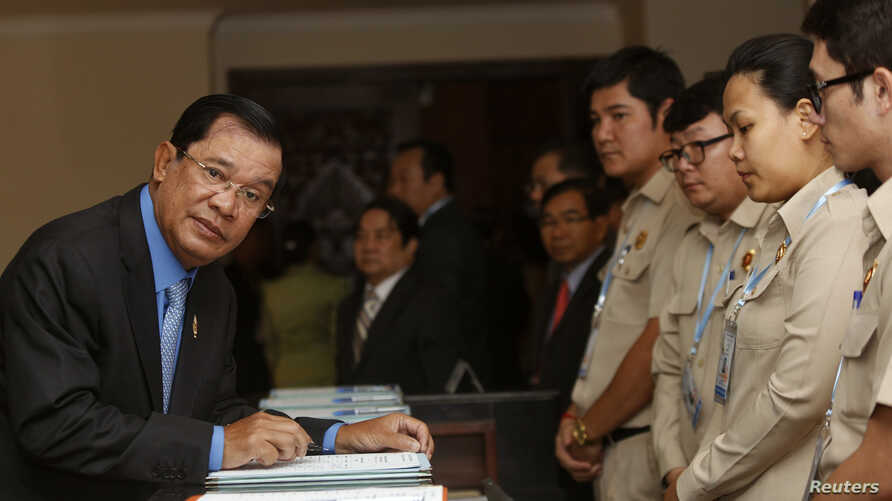 Cambodia's Prime Minister Hun Sen (L), arrives before Cambodia's Parliament session to vote on a rare shake up of his cabinet, at the National Assembly in Central Phnom Penh April 4, 2016. (REUTERS/Samrang Pring)