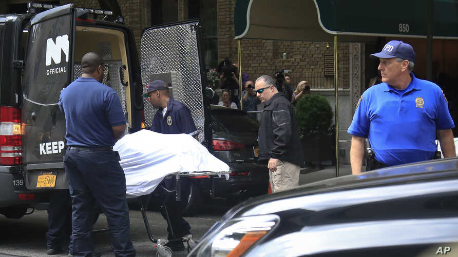 The body of designer Kate Spade is removed from her apartment building in New York on June 5, 2018.