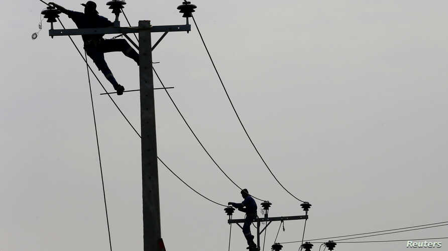 FILE - Employees from electricity board pull electric cables on top of electricity posts near a newly built road in Piliyandala, Sri Lanka, Nov. 29, 2016.