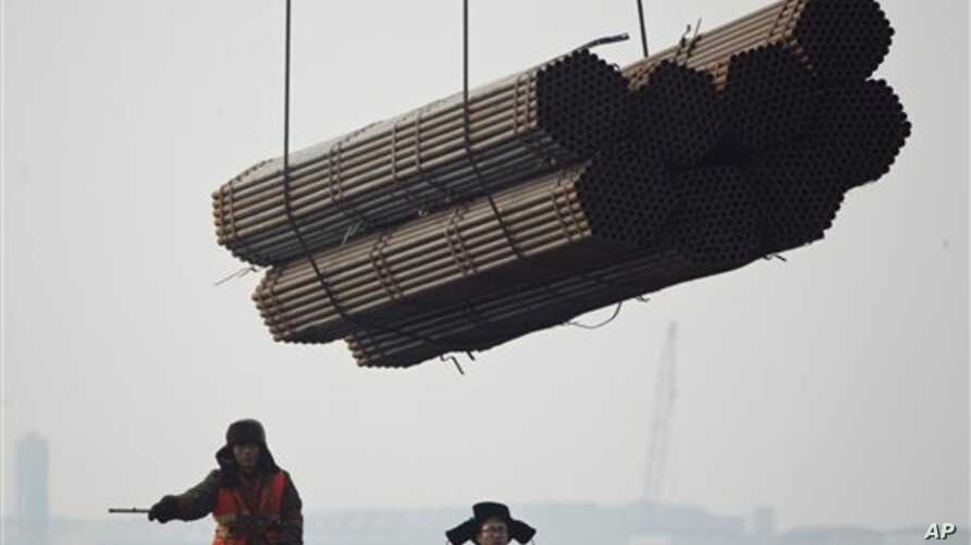Port workers watch as steel pipes are unloaded from freighter at Cao Feidian Port, Tangshan, Hebei province, China, Feb. 20, 2012.