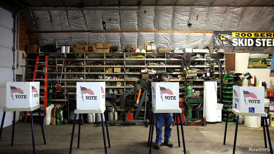 Voters cast their ballots at a polling station set up in a garage during the U.S. presidential election, near Fernald, Iowa, Nov. 8, 2016.