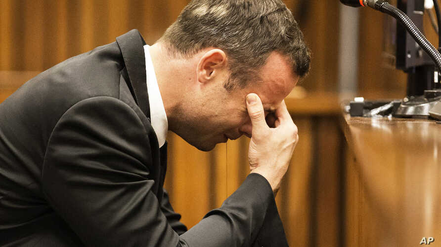 Oscar Pistorius puts his hand to his face while listening to evidence from a witness speaking about the morning of the shooting in court on the fourth day of his trial at the high court in Pretoria, March 6, 2014.