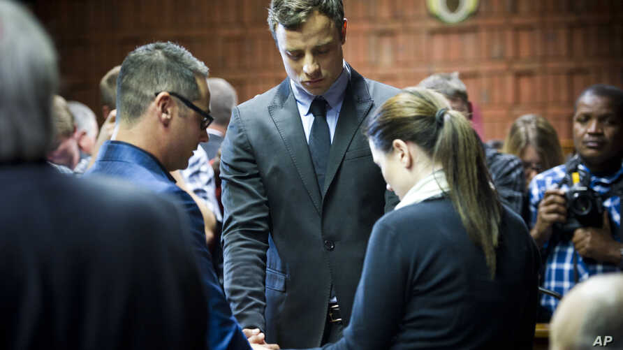 Oscar Pistorius cries as he prays with his sister Aimee and brother Carl in the magistrates court in Pretoria, South Africa, Augusst 19, 2013.