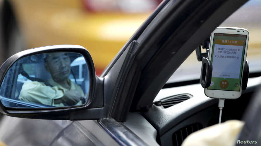 FILE - A taxi driver is reflected in a side mirror as he uses the Didi Chuxing car-hailing application in Beijing, China, Sept. 22, 2015.