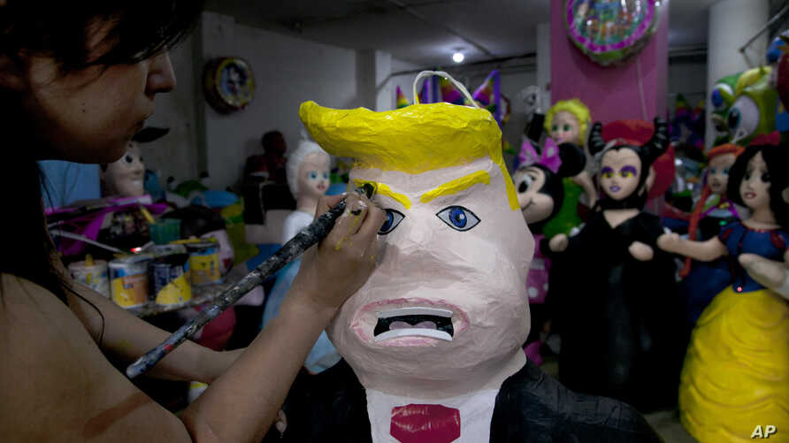 """FILE - Alicia Lopez Fernandez paints a pinata depicting Donald Trump at her family's store """"Pinatas Mena Banbolinos"""" in Mexico City, July 10, 2015. In a surprise move, Donald Trump will travel to Mexico Aug. 31 to meet with President Enrique Pena Nie"""
