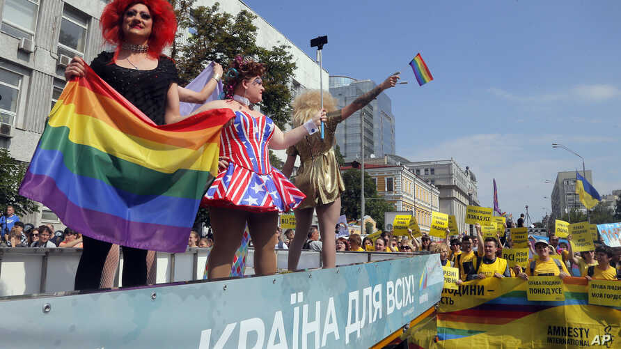 Gay and lesbian rights activists demonstrate as participants of the annual Gay Pride parade wave from a float in Kyiv, Ukraine, June 18, 2017.