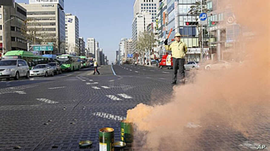 A South Korean government official controls traffic as part of a civil defense drill in Seoul, 15 Dec 2010