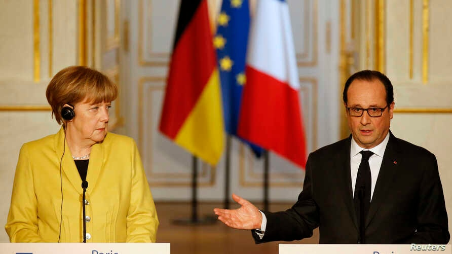German Chancellor Angela Merkel (L) listens to French President Francois Hollande during a joint news conference after talks in Paris, Feb. 20, 2015.