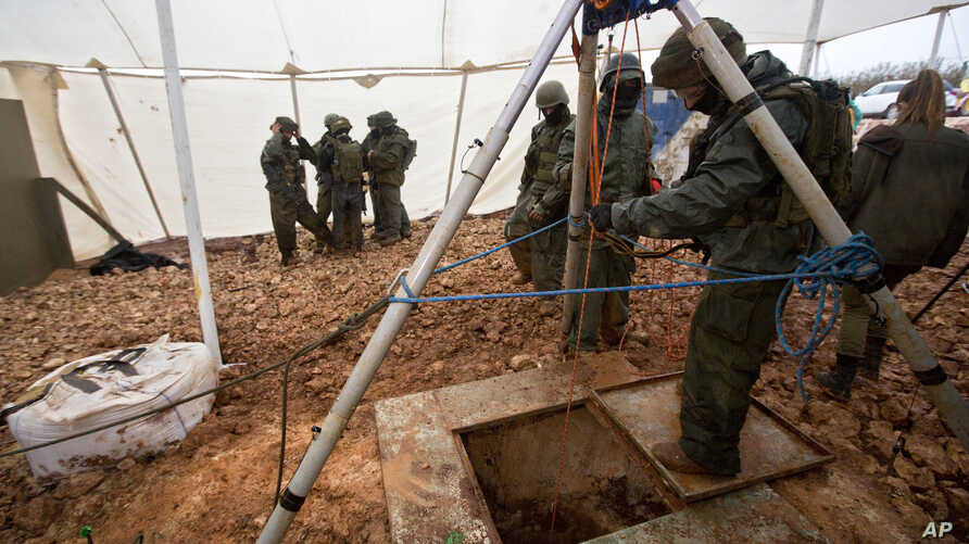 Israeli soldiers stand around the opening of a hole that leads to a tunnel that the army says crosses from Lebanon to Israel, near Metula, Dec. 19, 2018.