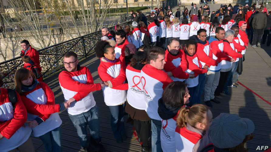 Volunteers hold hands on the Pont des Arts pedestrian bridge in central Paris to create a human chain as part of World AIDS Day, December 1, 2012.