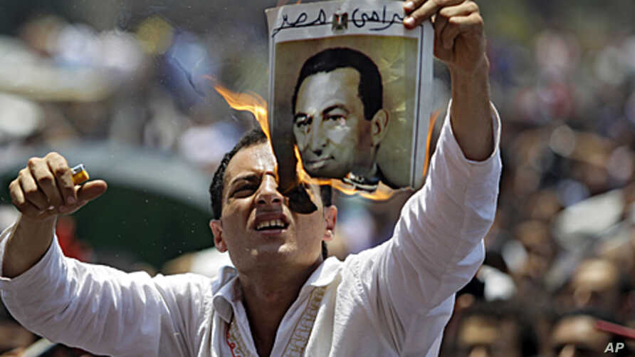 A man burns a picture of ousted Egyptian president Hosni Mubarak during a rally after Friday prayers in Tahrir Square, Cairo,  July 1, 2011