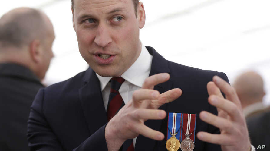 Britain's Prince William gestures as he meets veterans and serving members of the British armed forces at a reception following an unveiling of a national memorial honoring the Armed Forces and civilians who served their country during the Gulf War a