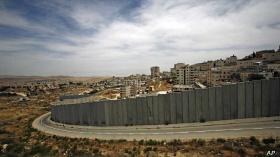 A section of the controversial Israeli barrier is seen from Jerusalem and shows the Shuafat refugee camp (R) in the West Bank near Jerusalem, and Pisgat Zeev (L) in an area Israel annexed to Jerusalem after capturing it in the 1967 Middle East war, M