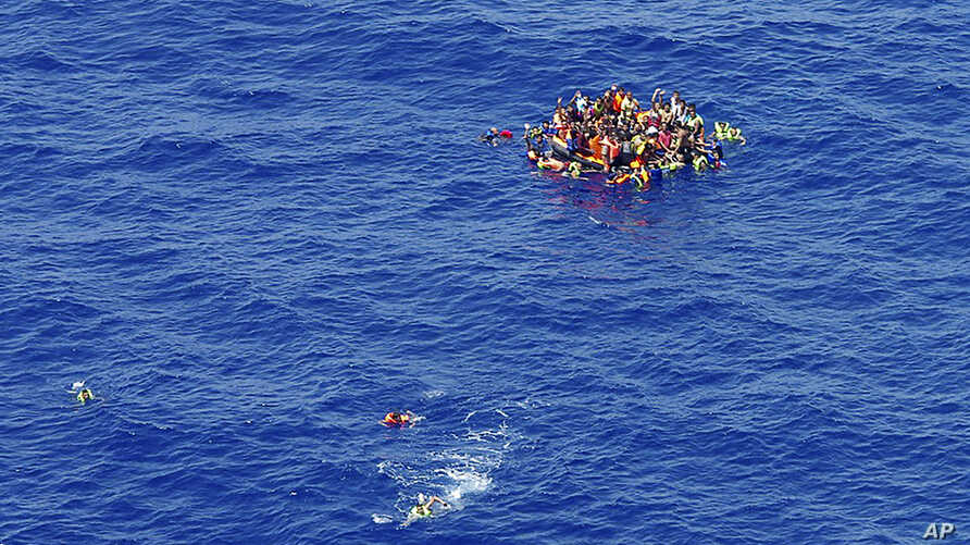 In this photo taken on Wednesday, Aug. 5, 2015 and made available Thursday, Aug. 6, migrants swim while others climbed onto a rescue dinghy wait for rescuers on the scene of the capsizing and sinking of a fishing boat in the Mediterranean sea off Lib