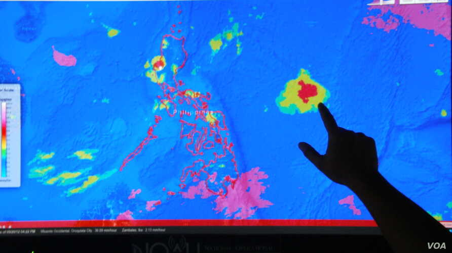 Project NOAH Executive Director Mahar Lagmay points at a satellite image of a tropical depression approaching the Philippines from the east at the National Institute of Geological Sciences at the University of the Philippines Diliman campus (in Metro