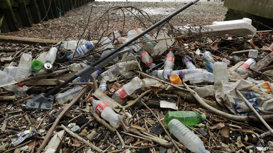 FILE - Plastic bottles and other plastics, including a mop, lie washed up on the bank of the River Thames in London, Britian, Feb. 5, 2018.
