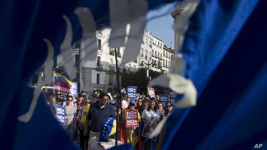 Seen through a hole in a torn Venezuelan flag, people gather to protest in support of families and friends in Venezuela during a protest in Madrid, Spain, April 19, 2017.  Opponents of Venezuelan President Nicolas Maduro called on people to take to t