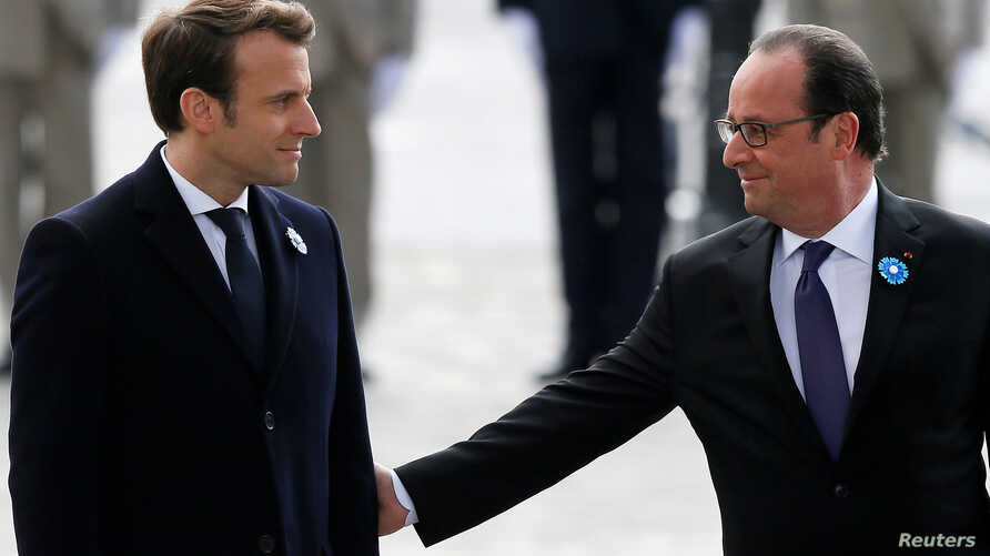 Outgoing French President Francois Hollande (R) reaches out to touch President-elect Emmanuel Macron, as they attend a ceremony to mark the end of World War II at the Tomb of the Unknown Soldier at the Arc de Triomphe in Paris, May 8, 2017.