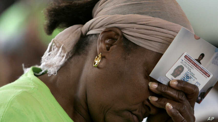 FILE - Marie Jean-Louis bows her head as she holds her Employment Authorization card and photographs of her family in Haiti during a vigil sponsored by Haitian Women of Miami at the Notre Dame Catholic Church in the Little Haiti neighborhood of Miami