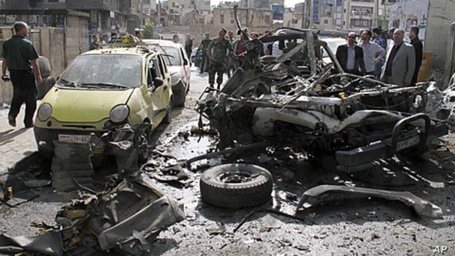 People look at destroyed and damaged vehicles after an explosion on al-Thawra Street in Damascus, Syria, May 5, 2012.