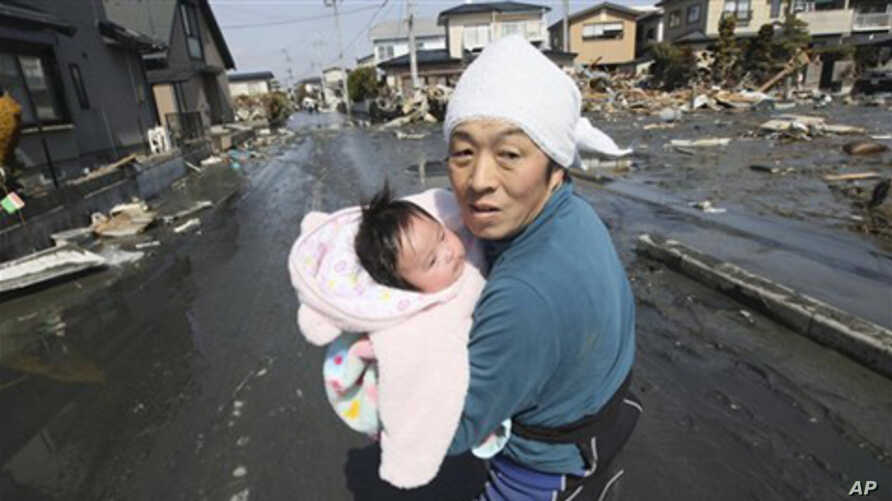 Upon hearing another tsunami warning, a father tries to flee for safety with his just reunited four-month-old baby girl who was spotted by Japan's Self-Defense Force member in the rubble of tsunami-torn Ishinomaki Monday, March 14, 2011.
