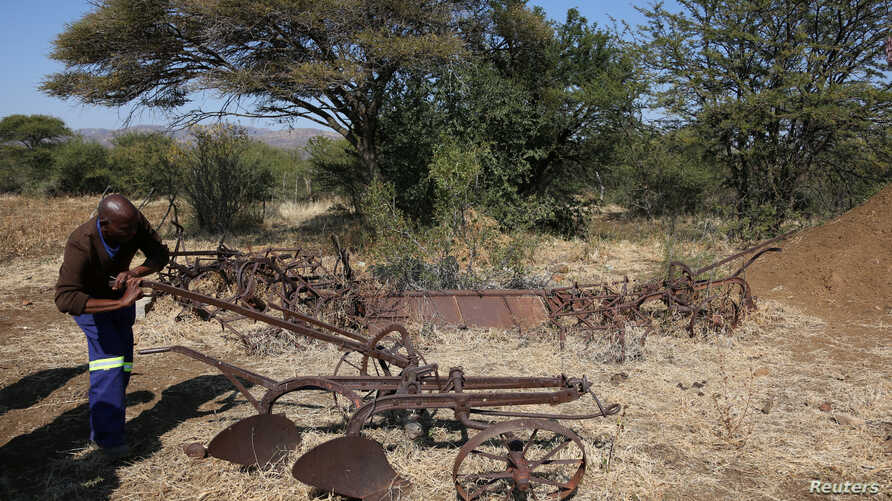 A villager inspects old farming equipment in Moruleng, a small mining community, in Rustenburg, Northwest province, South Africa, June 27, 2018.
