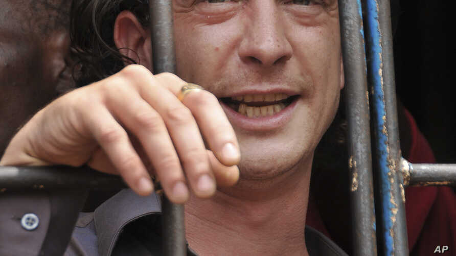 """David Cecil, the British producer of the play """"The River and the Mountain"""" concerning the condition of Uganda's gays, stands in a court cell in the capital Kampala, Uganda, September 13, 2012."""