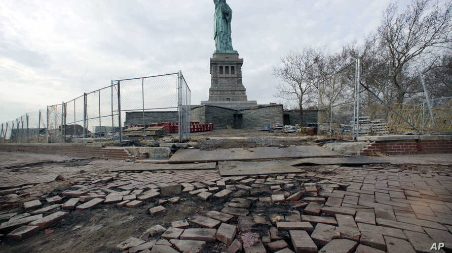 FILE - The Statue of Liberty stands beyond parts of a brick walkway damaged in Superstorm Sandy on Liberty Island in New York,  Nov. 30, 2012. With scientists forecasting sea levels to rise by anywhere from several inches to several feet by 2100, his