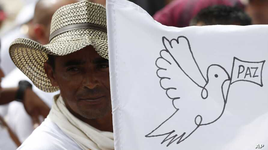 A rebel of the Revolutionary Armed Forces of Colombia, FARC, waves a white peace flag during an act to commemorate the completion of their disarmament process in Buenavista, Colombia, June 27, 2017.