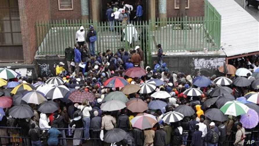 Zimbabweans queue in the rain outside immigration offices in Johannesburg, Wednesday, Dec. 15, 2010, as they wait to apply to become legal immigrants before the cut-off deadline and what they fear will be a wave of deportations in the new year.
