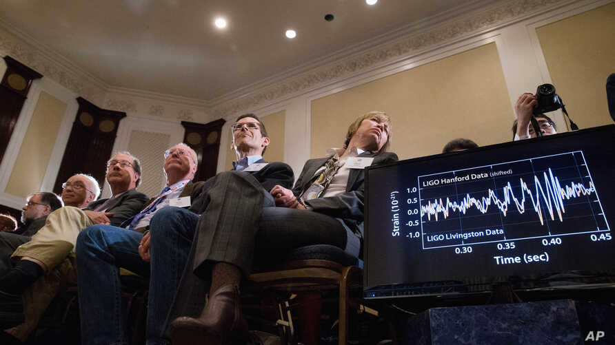 Audience members look at monitors displaying detected data which scientists say is proof of gravitational ripples, Thursday, Feb. 11, 2016, during a news conference at the National Press Club in Washington, just as Albert Einstein predicted a century