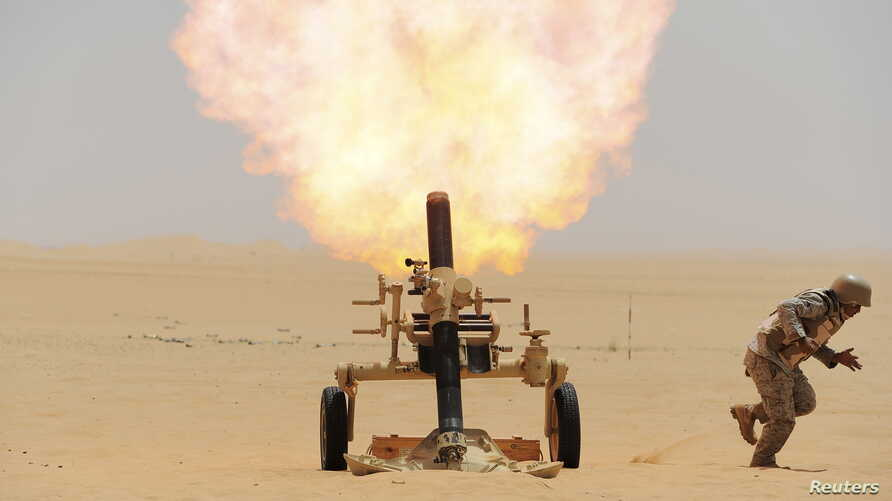 FILE - A Saudi soldier fires a mortar towards Houthi rebel positions, at the Saudi border with Yemen, April 21, 2015.