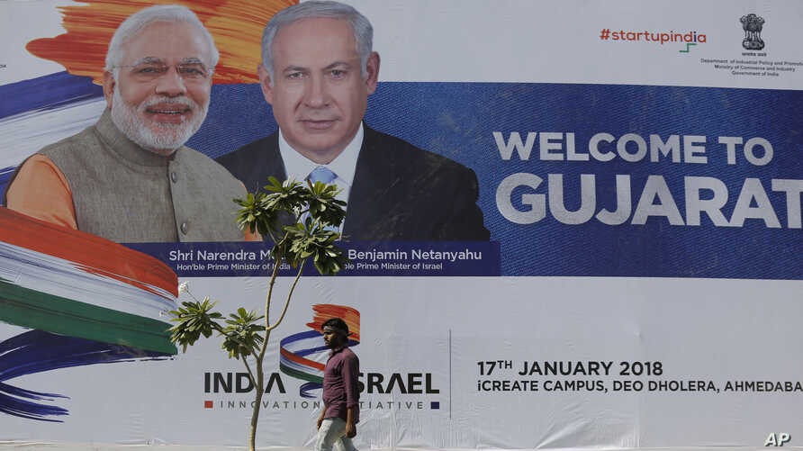 An Indian man walks past a hoarding put up to welcome Israeli Prime Minister Benjamin Netanyahu that features him along with Indian Prime Minister Narendra Modi at the International Centre for Entrepreneurship and Technology (iCreate) near Bavla in A