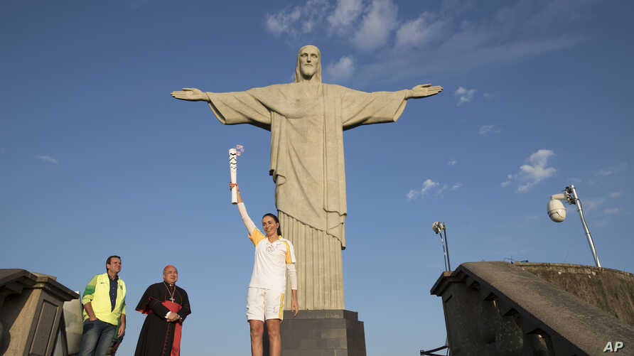 Brazil's former volleyball player Isabel Barroso Salgado carries the Olympic torch in front of the Christ the Redeemer statue on its way for the opening ceremony of Rio's 2016 Summer Olympics in Rio de Janeiro, Brazil, Aug. 5, 2016.