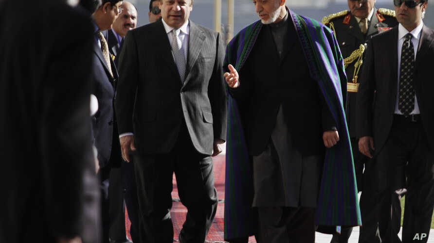 Afghan President Hamid Karzai, center right, talks with Pakistan's Prime Minister Nawaz Sharif while they inspect a guard of honor in Kabul, Afghanistan, Saturday, Nov, 2013.